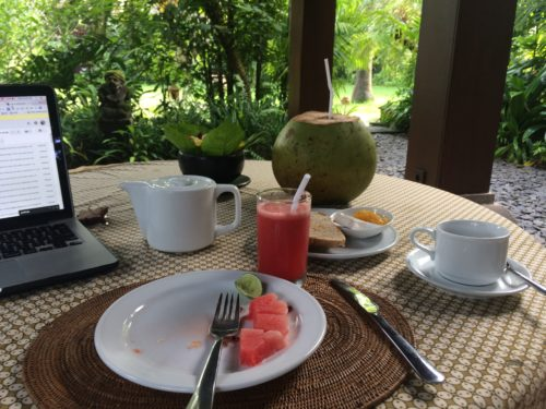 breakfast table with fruit, coffee, and coconut at Bali Purnati