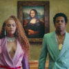 Still from Apeshit featuring Beyoncé in a purple suit next to Jay-Z in a turquoise suit, both looking forward with the Mona Lisa behind them