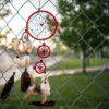 "Dreamcatcher hanging on fence outside a blurred image of ""Scaffold"" exhibit"