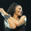 Closeup of Janet Jackson with microphone headset on over smile, in concert in 2011