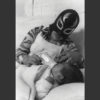 Lourdes Brobet's photograph of a mother in a wrestling mask feeding her baby a bottle