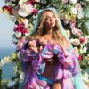 Beyoncé birth announcement photo by Awol Erizku - showing Beyoncé surrounded by colorful flowers, holding her twins.