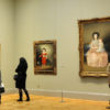Three viewers with their back turned towards the photograph, looking at three portrait paintings in gilded frames at the Met