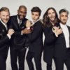 Five stars of Queer Eye stand together in matching black suits, posing for the camera, smiling