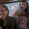 Still from Smoke Signals featuring Evan Adams with long braided hair and glasses and Adam Beach with long hair, both looking into a car window