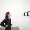 A lone, young woman in black coveralls holds a hammer and looks at a museum wall featuring three framed images